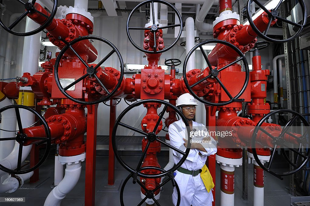 A Keppel Corp. employee stands next to valve wheels and pipework on the deck of the Transocean Siam Driller jackup rig, built for Transocean Ltd., during a naming ceremony at the Keppel FELS shipyard in Singapore, on Saturday, Feb. 2, 2013. Keppel Corp.'s FELS unit received a combined $1.5 million bonus for completing the construction of two drilling rigs ahead of time, the company said in a statement. Photographer: Munshi Ahmed/Bloomberg via Getty Images