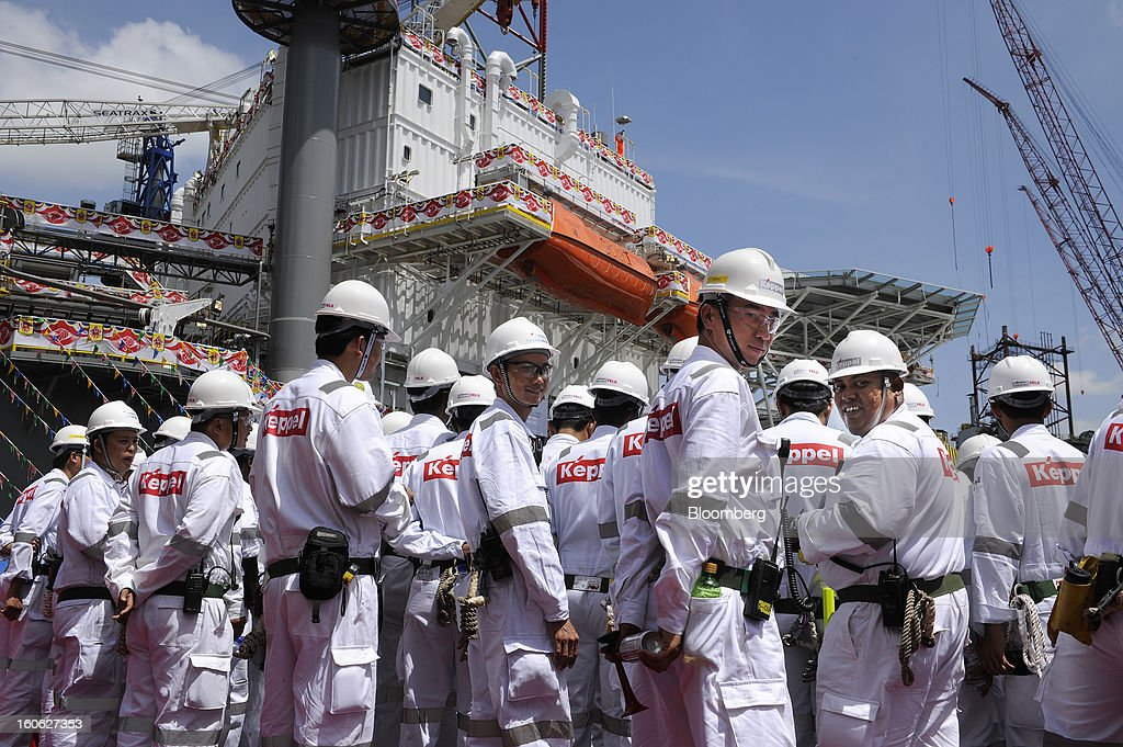 Keppel Corp. employees gather for a group photograph on the deck of the Transocean Siam Driller jackup rig, built for Transocean Ltd., during a naming ceremony at the Keppel FELS shipyard in Singapore, on Saturday, Feb. 2, 2013. Keppel Corp.'s FELS unit received a combined $1.5 million bonus for completing the construction of two drilling rigs ahead of time, the company said in a statement. Photographer: Munshi Ahmed/Bloomberg via Getty Images