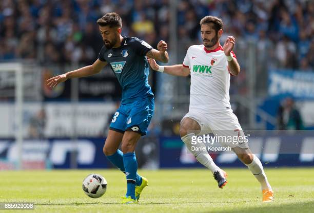 Kerem Damirbay of Hoffenheim is challenged by Halil Altintop of Augsburg during the Bundesliga match between TSG 1899 Hoffenheim and FC Augsburg at...