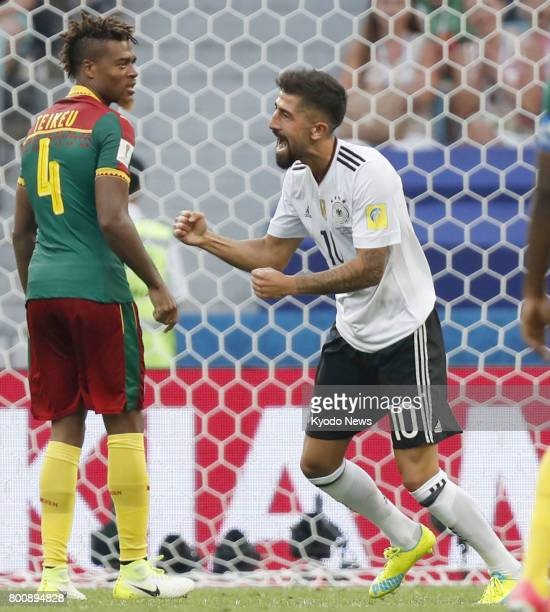 Kerem Demirbay celebrates after scoring Germany's opening goal as Adolphe Teikeu of Cameroon looks on during the second half of a Group B match at...