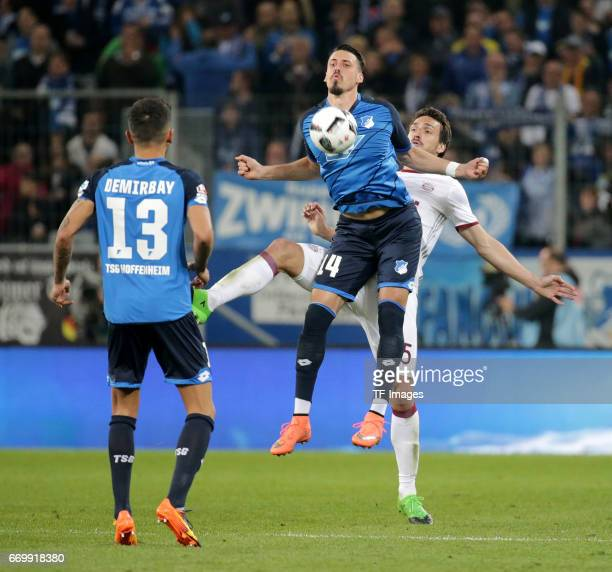 Kerem Demirbay of Hoffenheim and Sandro Wagner of Hoffenheim and Mats Hummels of Munich battle for the ball during the Bundesliga match between TSG...