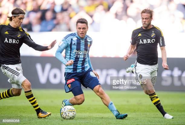 Kerim Mrbati of Djurgardens IF between Kristoffer Olsson and Daniel Sundgren of AIK during the Allsvenskan match between AIK and Djurgardens IF at...
