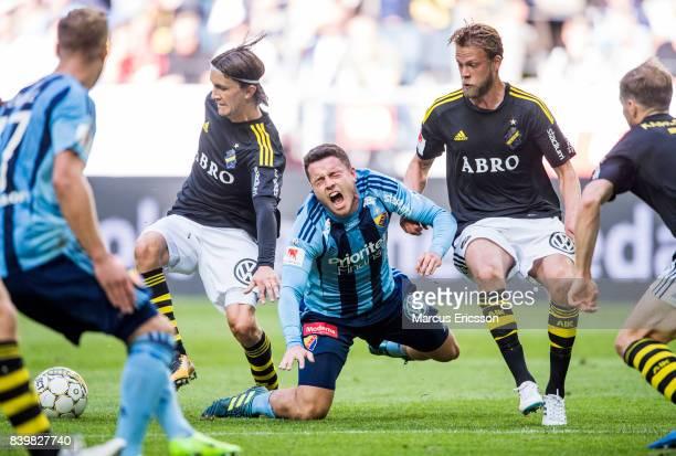 Kerim Mrbati of Djurgardens IF falls against Kristoffer Olsson of AIK during the Allsvenskan match between AIK and Djurgardens IF at Friends arena on...