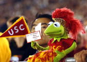 A Kermit the Frog doll is dressed in USC colors with a banner making reference to the current and former school mascots of the Stanford Cardinal...