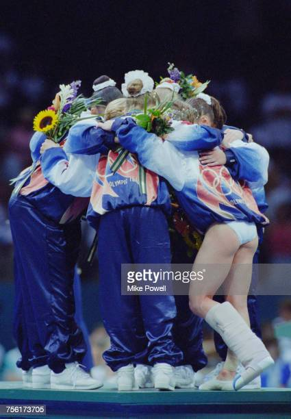 Kerri Strug of the United States with her leg in plaster joins in the group celebrations with her team mates on the podium after winning the artistic...