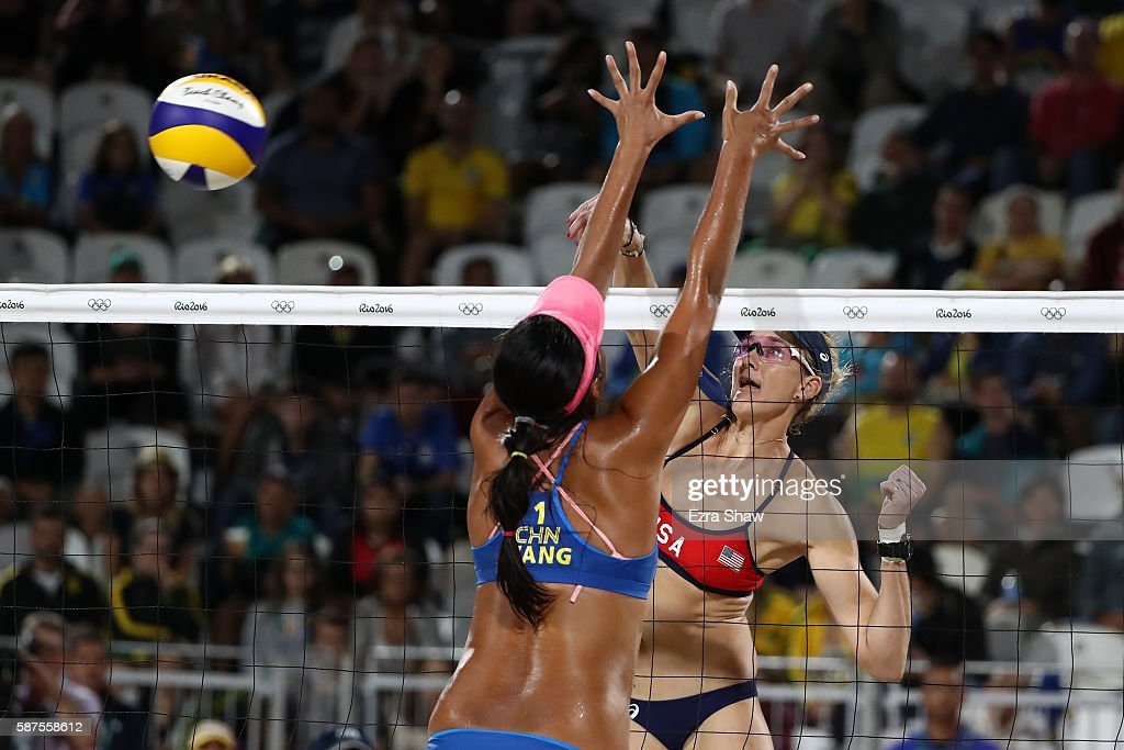 Kerri Walsh Jennings of United States spikes the ball as Fan Wang of China attempts to block during the Women's Beach Volleyball preliminary round...