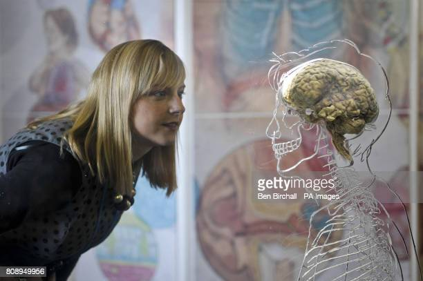 Kerrie Grist from @Bristol science attraction inspects a real human brain suspended in liquid with a toscale skeleton central nervous system and...