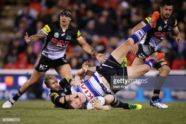 Kerrod Holland of the Bulldogs is tackled by Peter Wallace of the Panthers during the round 21 NRL match between the Penrith Panthers and the...