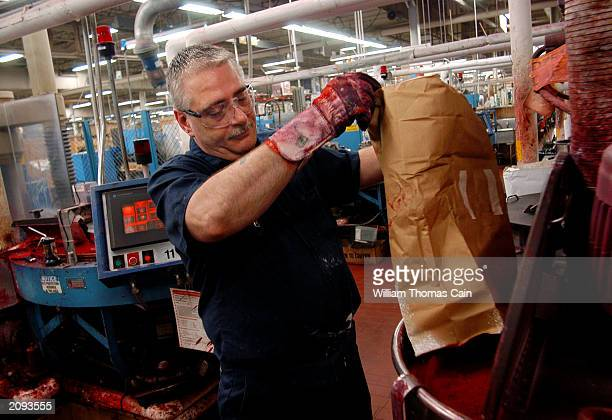 Kerry Clauss adds red color to a kettle of wax that will become crayons at Binney and Smith Inc the manufacturer of Crayola crayons June 18 2003 in...