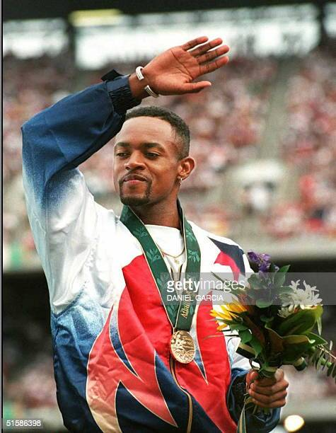Kerry Harrison of the United States waves on the podium after receiving gold for the men's triple jump 28 July at the Olympic Stadium in Atlanta...