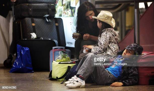 Kerry Morre amd her two children Lucia Zarza Bell and Nathan Zarza Bell wait at Glasgow Airport in Scotland following a number of flight...