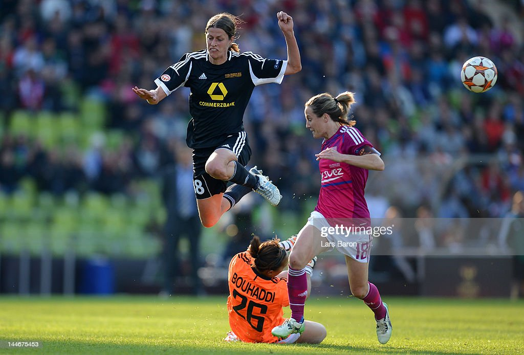 Kerstin Garefrekes of Frankfurt jumps over goalkeeper Sarah Bouhaddi of Lyon next to Sonia Bompastor of Lyon during the UEFA Women's Champions League Final between Olympique Lyonnais and 1. FFC Frankfurt at Olympiastadion on May 17, 2012 in Munich, Germany.