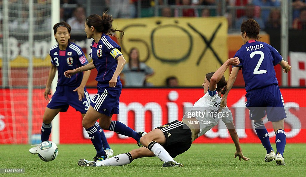 Kerstin Garefrekes (C) of Germany and Homare Sawa (L) of Japan battle for the ball during the FIFA Women's World Cup 2011 Quarter Final match match between Germany and Japan at Wolfsburg Arena on July 9, 2011 in Wolfsburg, Germany.