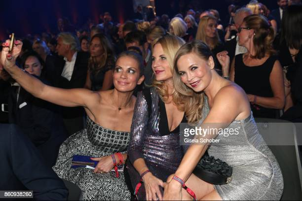 Kerstin Linnartz fashion designer Sonja Kiefer and Regina Halmich take a selfie during the 'Tribute To Bambi' gala at Station on October 5 2017 in...