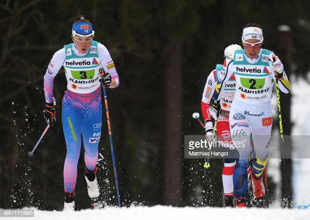 Kerttu Niskanen of Finland and Charlotte Kalla of Sweden compete during the Women's Cross Country 4x5km Relay at the FIS Nordic World Ski...