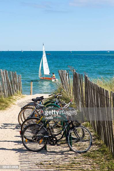 Kervillen beach in La Trinite sur Mer bikes on the seaside along a path leading to the beach Optimist sailing dinghy for sailing learning with view...