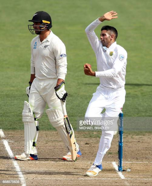 Keshav Maharaj of South Africa bowls next to Colin de Grandhomme of New Zealand during day four of the third Test cricket match between New Zealand...