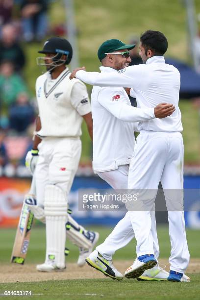 Keshav Maharaj of South Africa celebrates with captain Faf du Plessis after taking the wicket of Jeet Raval of New Zealand during day three of the...