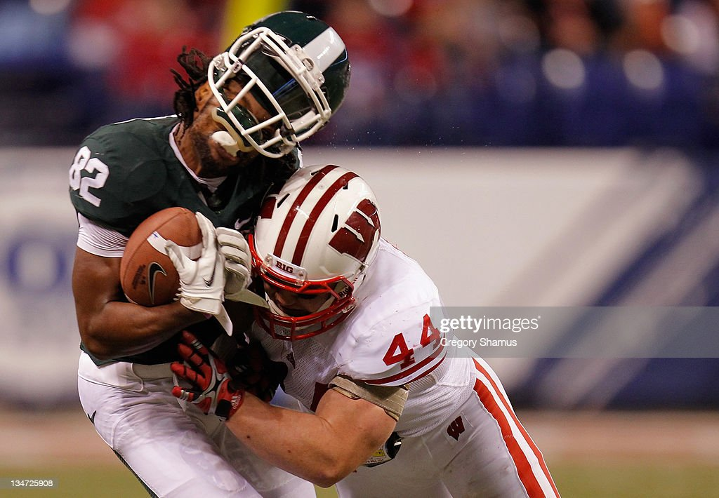 Keshawn Martin #82 of the Michigan State Spartans loses his helmet as he is hit by Chris Borland #44 of the Wisconsin Badgers during the third quarter of the Big 10 Conference Championship Game at Lucas Oil Stadium on December 3, 2011 in Indianapolis, Indiana.