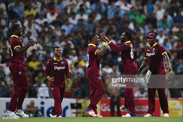 Kesrick Williams of West Indies celebrates with Dwayne Bravo taking the wicket of Khalid Latif of Pakistan during the third T20 International match...