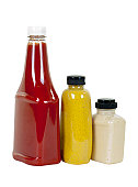 Tomato ketchup, spicy brown mustard and creamy horseradish in bottles, angle view; isolated on white background