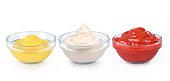ketchup, mustard and mayonnaise in glass bowls