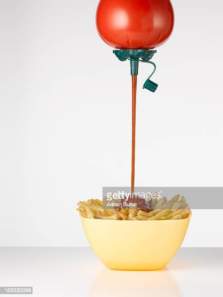 Ketchup pouring onto chips.