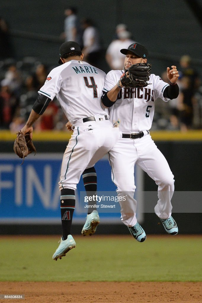 Ketel Marte #4 and Gregor Blanco #5 of the Arizona Diamondbacks celebrate after closing out the MLB game against the San Francisco Giants at Chase Field on September 26, 2017 in Phoenix, Arizona.