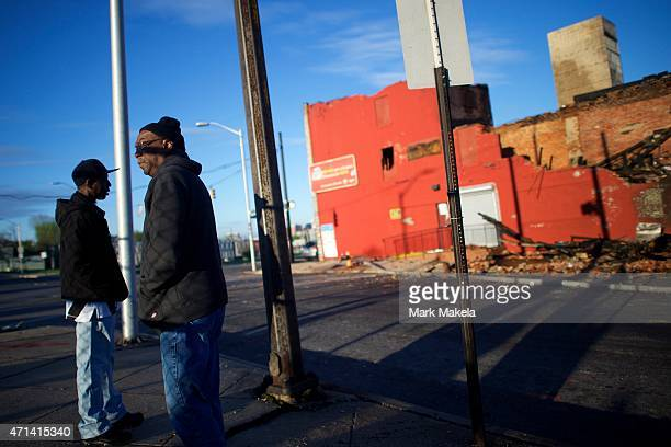 Ketih Garris and Larry James stare at the charred remains of a bus and senior center set ablaze during night riots on April 28 2015 in Baltimore...