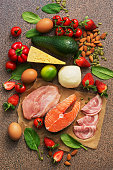 Keto diet concept.Healthy foods low in carbohydrates. Salmon, chicken, vegetables, strawberries, nuts, eggs and tomatoes, cutting board Top view
