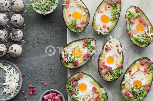 Keto diet dish: Avocado boats with ham cubes, quail eggs, cheese and cress sprouts : Stock Photo
