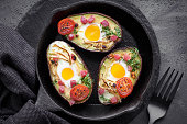 Keto diet dish: Avocado boats with ham cubes, quail eggs, cheese and cress sprouts on cast iron skillet with towel on dark background, top view