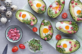 Keto diet dish: Avocado boats with quail eggs, ham cubes and cress sprouts on light stone serving board with ingredients around