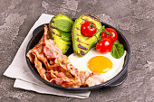 Grilled bacon and avocado, fried eggs with spinach and cherry tomatoes on vintage wooden cutting board. Gray concrete background. Ketogenic diet. Low carb high fat breakfast. Healthy food concept