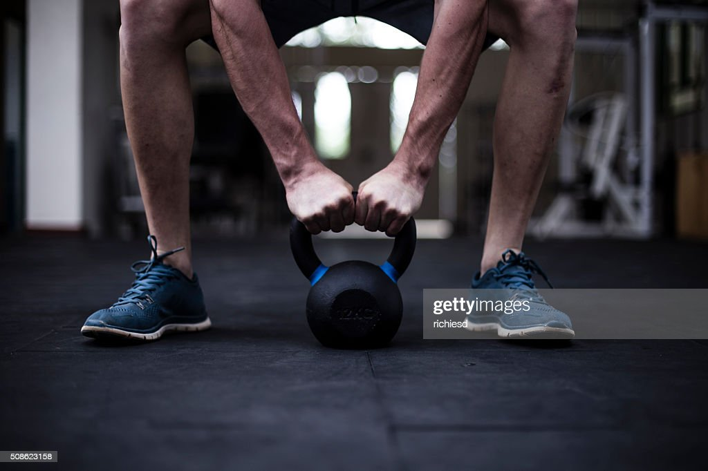 Kettle bell exercises at the gym : Stock Photo