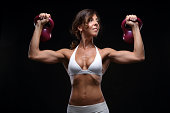 Attractive woman exercising with kettlebells in front of black background