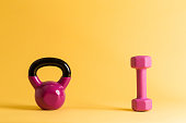 Kettlebell and dumbbell on a yellow background