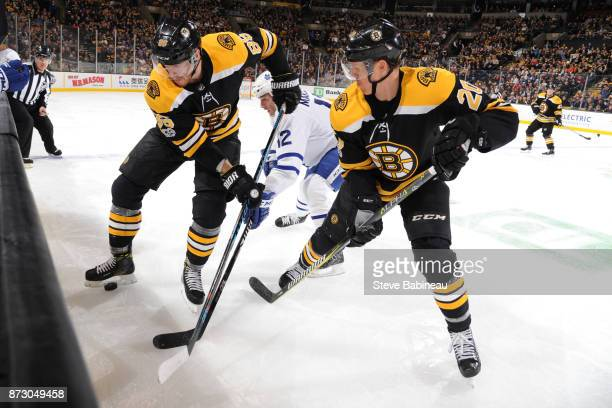 Kevan Miller and Riley Nash of the Boston Bruins fights for the puck against Patrick Marleau of the Toronto Maple Leafs at the TD Garden on November...