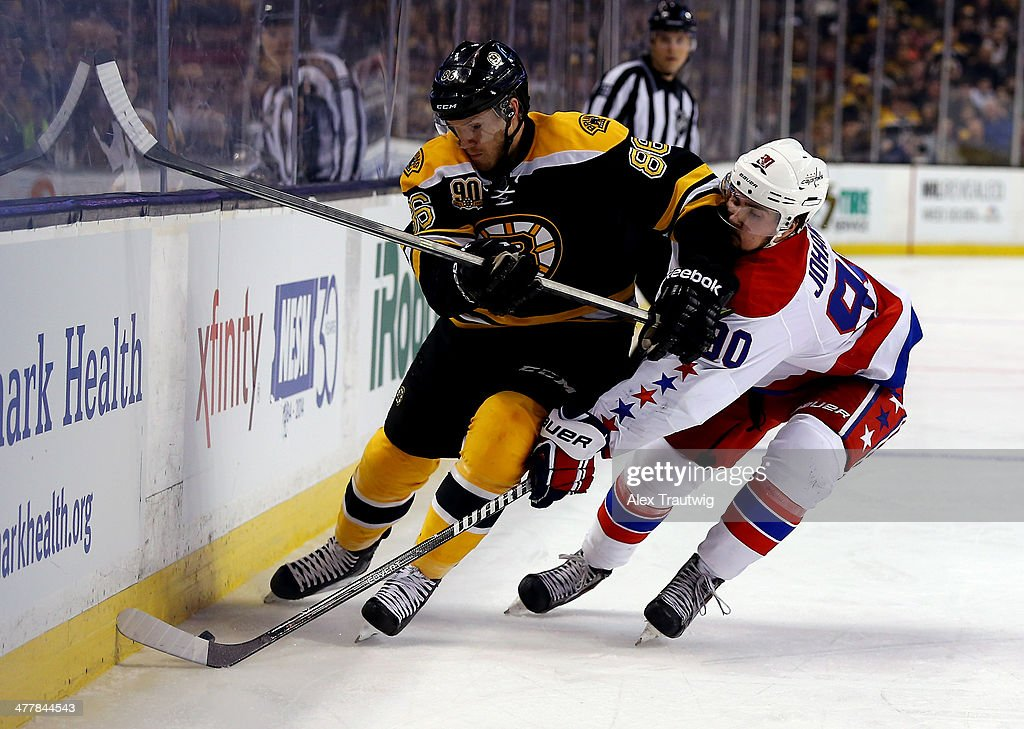 Kevan Miller #86 of the Boston Bruins and Marcus Johansson #90 of the Washington Capitals go for the puck during a game at the TD Garden on March 1, 2014 in Boston, Massachusetts.