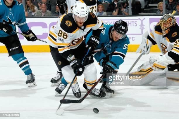 Kevan Miller of the Boston Bruins and Mikkel Boedker of the San Jose Sharks scramble for the puck at SAP Center on November 18 2017 in San Jose...