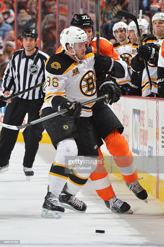 Kevan Miller of the Boston Bruins checks Jay Rosehill of the Philadelphia Flyers at the Wells Fargo Center on January 25 2014 in Philadelphia...