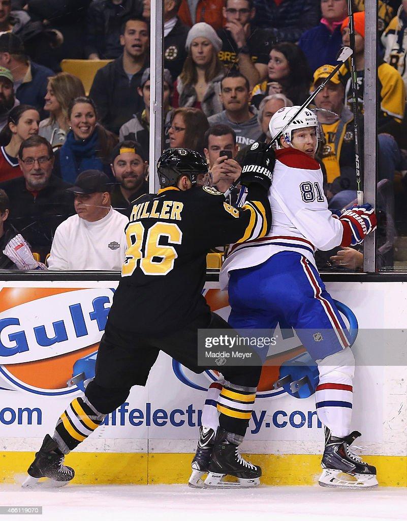 Kevan Miller #86 of the Boston Bruins checks Lars Eller #81 of the Montreal Canadiens into the boards at TD Garden on February 8, 2015 in Boston, Massachusetts.
