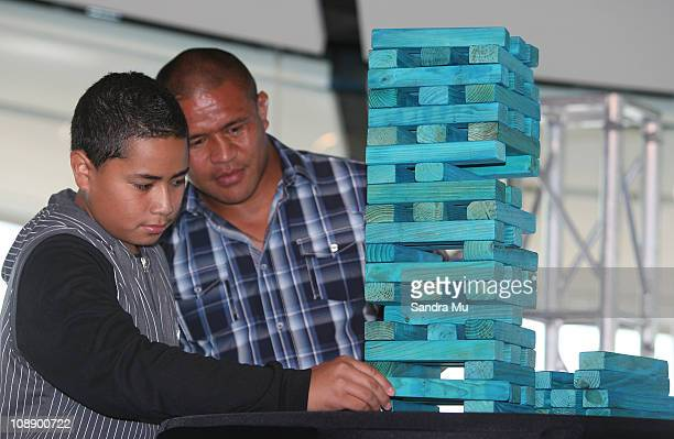 Keven Mealamu of the Blues watches Super Fan Jeffery Aiolupotea make a move in a Super Rugby captain's Jenga challenge during the 2011 Super Rugby...