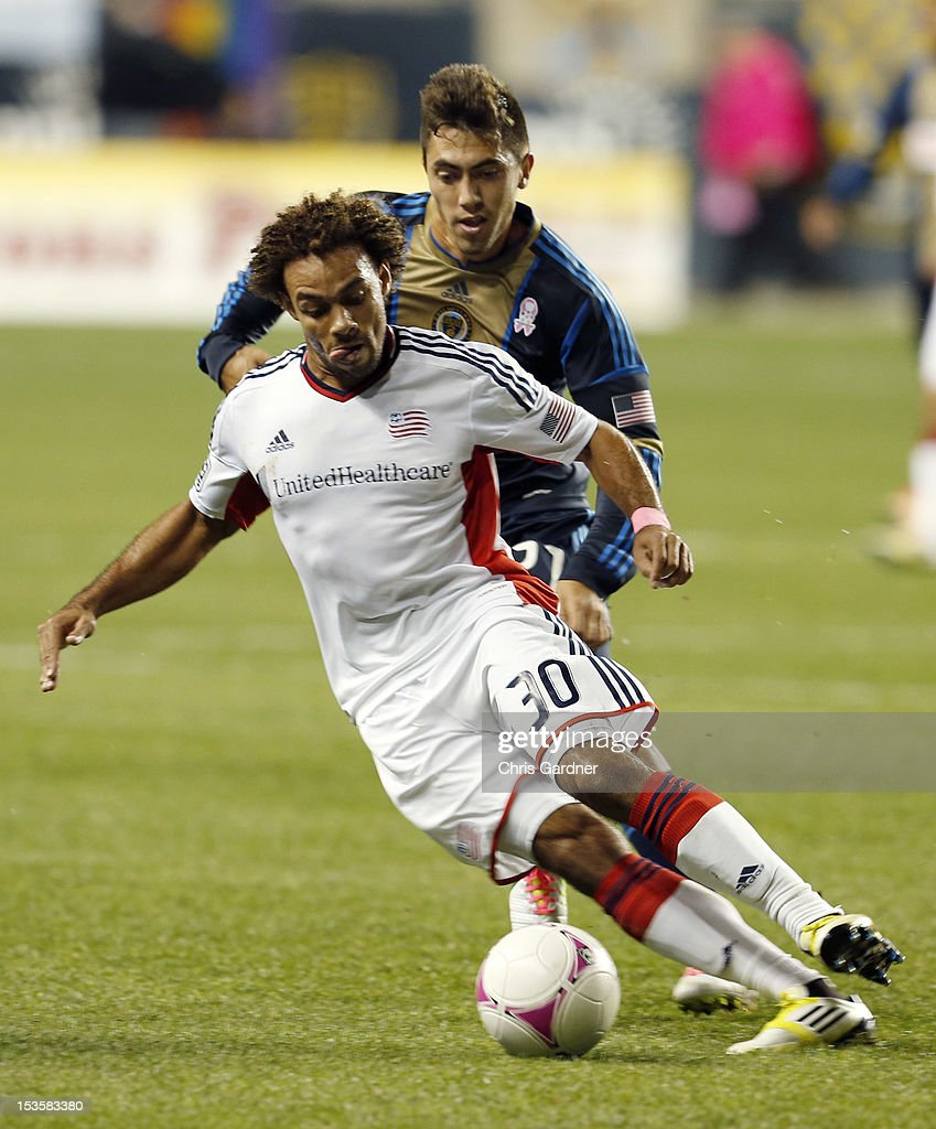 Kevin Alston #30 of the New England Revolution keeps the ball away from Michael Farfan #21of the Philadelphia Union at PPL Park on October 6, 2012 in Chester, Pennsylvania.