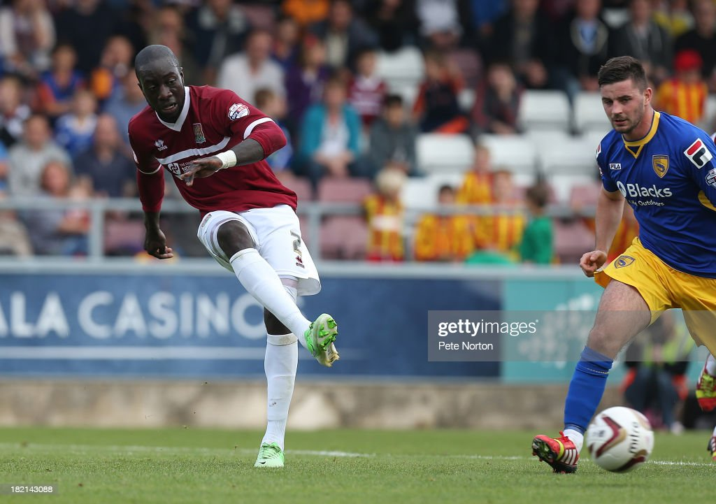 Kevin Amankwaah of Northampton Town plays the ball watched by Padraig Armond of Morecambe during the Sky Bet League Two match between Northampton Town and Morecambe at Sixfields Stadium on September 28, 2013 in Northampton, England.