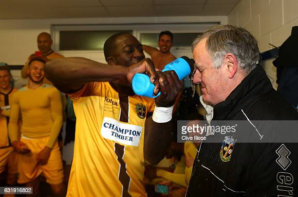 Kevin Amankwaah of Sutton United pours water over Clive Baxter club kitman as they celerbate after the Emirates FA Cup third round replay between AFC...