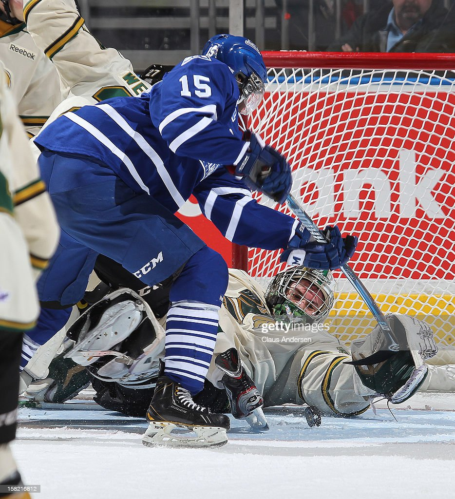 Kevin Bailie #30 of the London Knights stops a scoring attempt by Josh Burnside #15 of the Mississauga Steelheads in an OHL game on December 9, 2012 at the Budweiser Gardens in London, Ontario, Canada. The Knights defeated the Steelheads 5-2 and tied their franchise record of 18 straight wins.