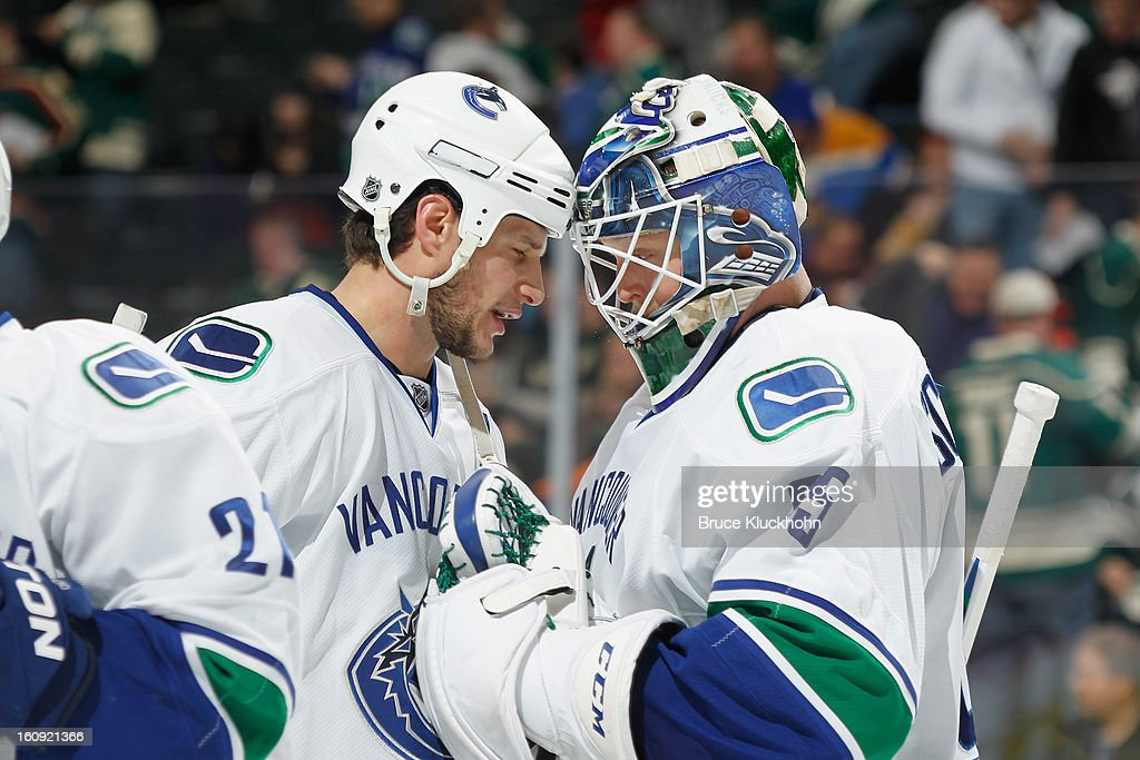 Kevin Bieksa #3 and goalie Cory Schneider #35 of the Vancouver Canucks celebrate after defeating the Minnesota Wild on February 7, 2013 at the Xcel Energy Center in St. Paul, Minnesota.