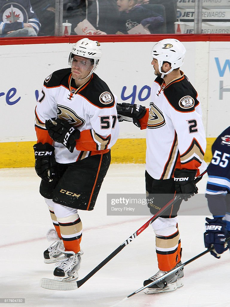 Kevin Bieksa of the Anaheim Ducks helps teammate David Perron towards the locker room after injuring himself with a fall against the boards during...