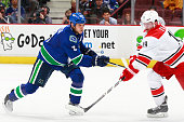 Kevin Bieksa of the Vancouver Canucks checks Jiri Tlusty of the Carolina Hurricanes during their NHL game against the Carolina Hurricanes at Rogers...